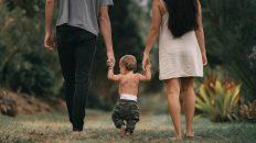 Un niño caminando con sus padres